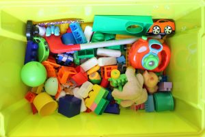 storing the childrens toys in robust green attached lid containers